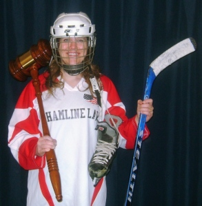 Minneapolis Department of Civil Right's Intern Liz Stoneburg sports hockey gear courtesy of Hamline Law's Res Ipsa Hockey Team and Team Captain Sten Schuler. Hamline Law's hockey team welcomes female players.